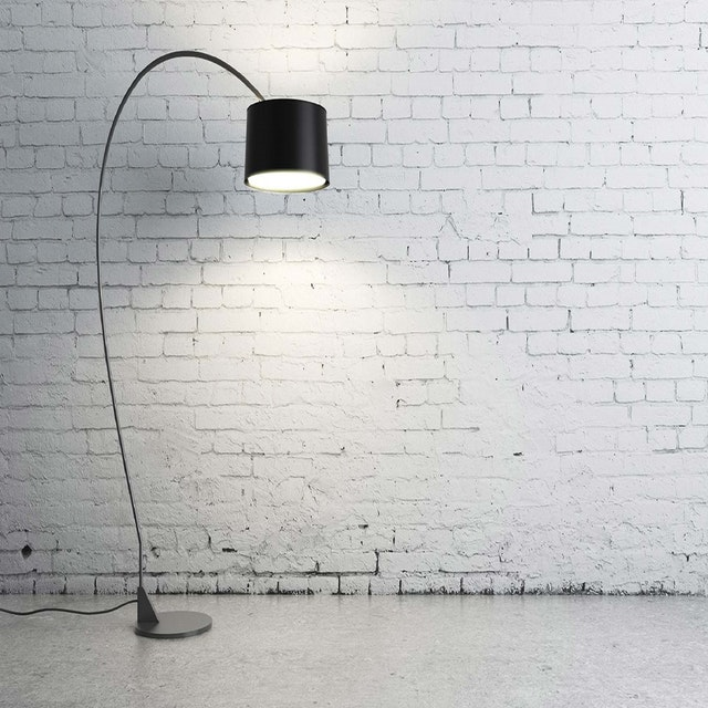 a black lamp left in an empty white room
