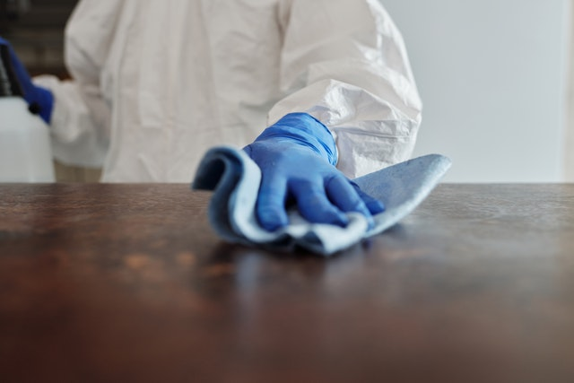 a man in a protective suit cleaning a table